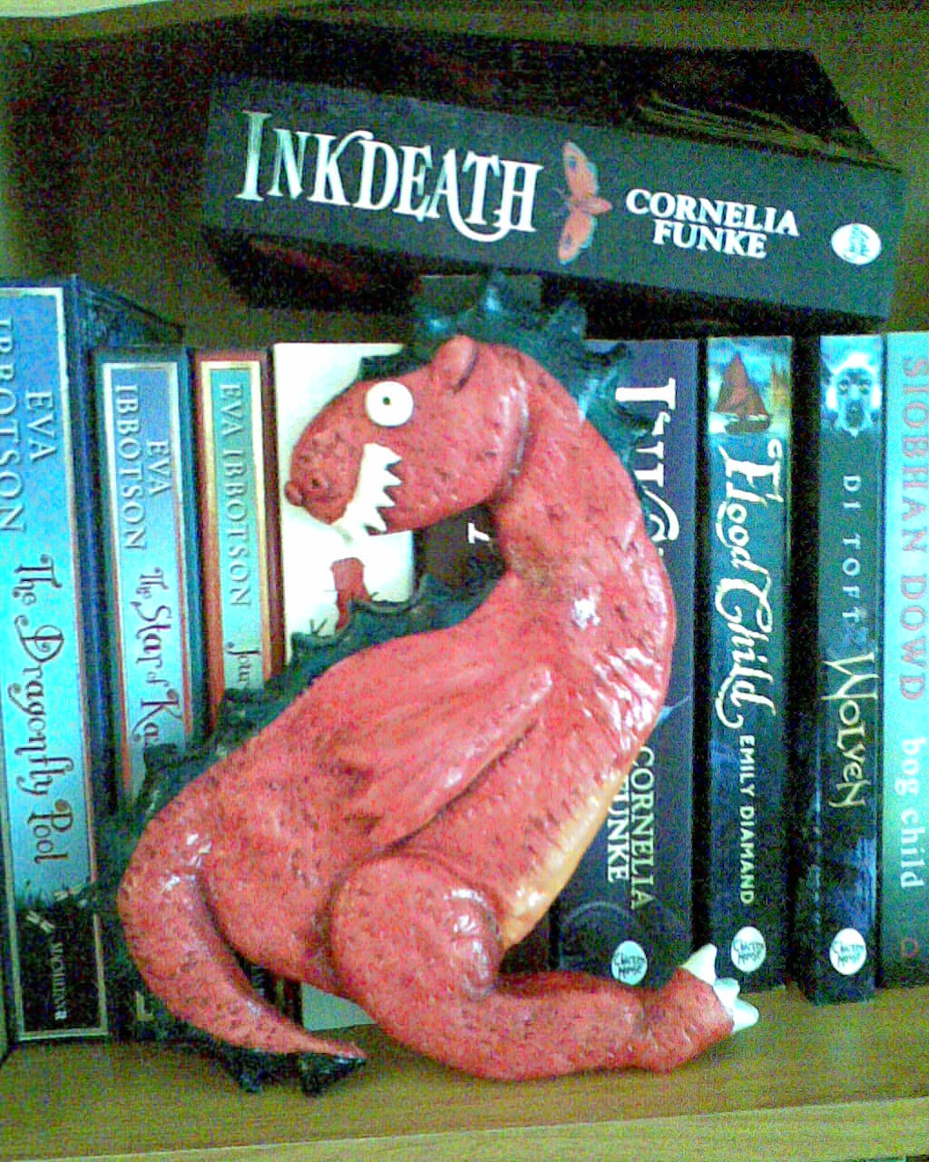 Photo of dough dragon and books on shelf